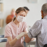 Portrait of young female nurse vaccinating senior man in vaccination center or medical clinic, copy space